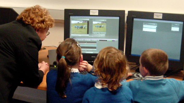 Photo of pupils editing with the help of a teacher