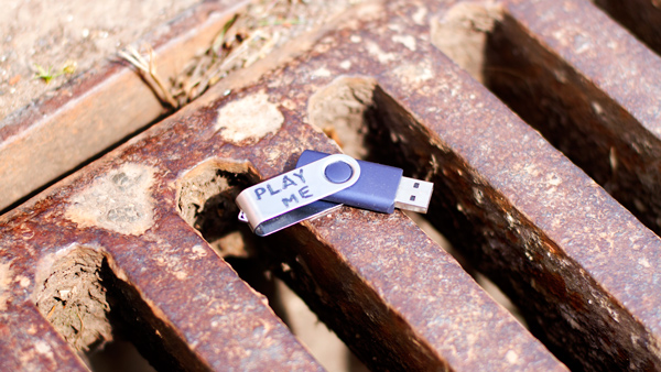 Photo of a USB pen drive on a drain labelled play me