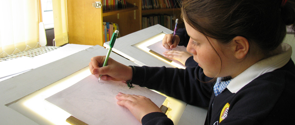Photo of a pupil drawing at a lightbox