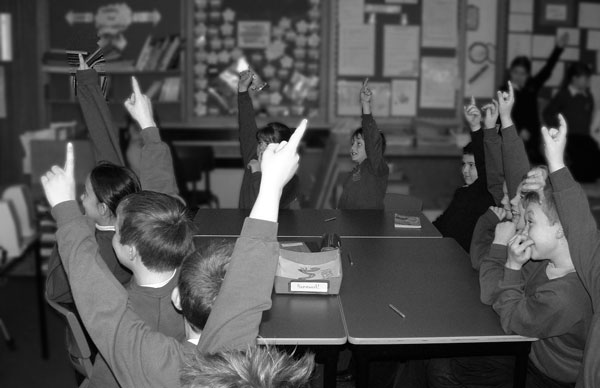 Children in the classroom with their hands up