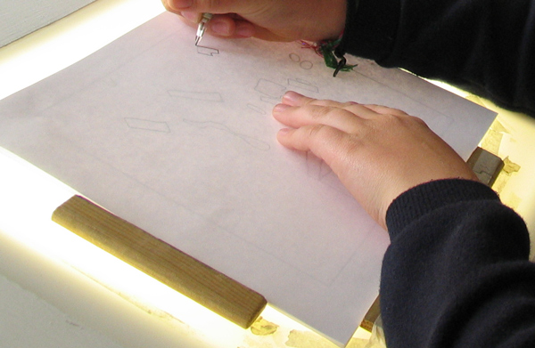 Photo close up of hands drawing at a lightbox