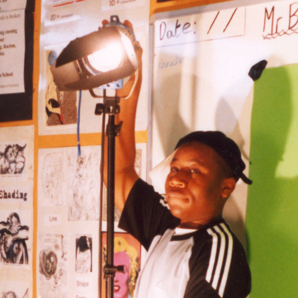 Photo of boy adjusting a film light in a non safe way